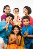 拿着Ganapati阁下的Ganesha或雕象Ganesh节日或chaturthi的,欢迎神印地安逗人喜爱的孩子 亚裔小男孩和g 免版税库存照片