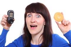 拿着glucometer和蛋糕的惊奇的妇女 库存照片