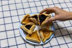 拿着Hamantash普珥节蓝莓和杏子在套色板的妇女手果酱曲奇饼在蓝色和白色桌布 库存图片