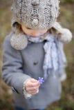 拿着hepatica花的小小孩女孩 免版税库存照片