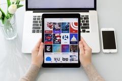 拿着iPad的妇女手赞成与普遍的新闻应用 库存图片