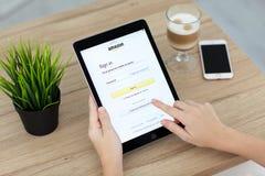 拿着iPad的妇女赞成与网上购物服务亚马逊 图库摄影