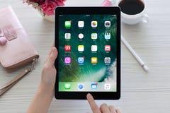 拿着iPad赞成空间的妇女灰色与墙纸IOS 10 库存图片