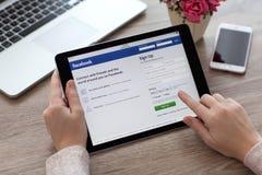 拿着iPad赞成空间的妇女灰色与福利事业Facebook 库存照片
