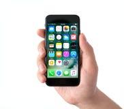 拿着iPhone 7乌黑IOS 10的被隔绝的人手 图库摄影