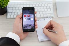 拿着iPhone 6空间的商人灰色与新闻应用 免版税库存照片
