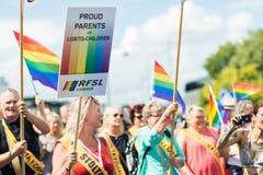 拿着LGBT孩子的标志骄傲的父母的愉快的人群挥动的彩虹旗子的妇女在斯德哥尔摩骄傲游行期间 图库摄影