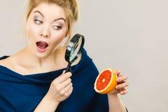 拿着magniferlooking的葡萄柚的妇女 库存照片