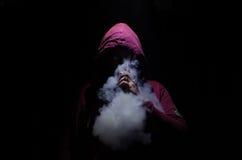 拿着mod的Vaping人 蒸气云彩  黑色背景 Vaping与很多烟的一根电子香烟 免版税库存照片