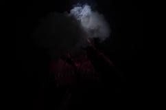 拿着mod的Vaping人 蒸气云彩  黑色背景 Vaping与很多烟的一根电子香烟 免版税库存图片