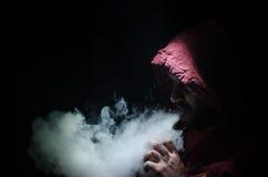拿着mod的Vaping人 蒸气云彩  黑色背景 Vaping与很多烟的一根电子香烟 库存照片
