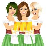 拿着oktoberfest党的三位美丽的女服务员啤酒杯敬酒穿少女装 免版税库存照片