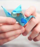拿着origami起重机的孩子 免版税库存图片