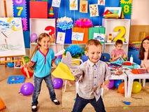 拿着origami飞机的小组孩子在幼儿园 免版税库存图片