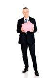 拿着piggybank的全长快乐的商人 免版税库存图片