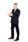 拿着piggybank的全长迷茫的商人 免版税库存照片