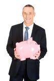 拿着piggybank的快乐的商人 免版税图库摄影