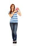 拿着piggybank的愉快的少年妇女 免版税库存图片