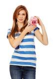 拿着piggybank的愉快的少年妇女 图库摄影