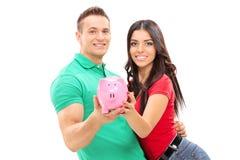 拿着piggybank的年轻夫妇 免版税库存照片