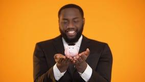 拿着piggybank,银行业务,储蓄的快乐的美国黑人的商人 股票视频