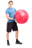 拿着pilates球的一位年轻男性运动员的全长画象 库存照片