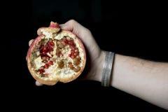 拿着pommegranate的人 库存图片