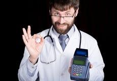 拿着pos终端,听诊器的医生的特写镜头portret在他的脖子上 他做与您的手指的一个好标志 免版税图库摄影
