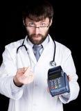 拿着pos终端,听诊器的医生的特写镜头portret在他的脖子上 他摩擦他的拇指和食指 图库摄影