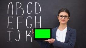 拿着prekeyed片剂,在黑板,创新的字母表的微笑的老师 影视素材