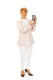 拿着sandglass的微笑年长女商人 免版税库存照片