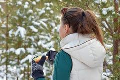 拿着sandwitch和咖啡杯的少妇在冬天森林里 免版税库存图片