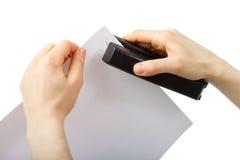 拿着stepler和纸的手 免版税图库摄影