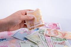 拿着Turksh里拉钞票的手手中 免版税库存照片