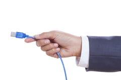 拿着USB缆绳的商人手 免版税库存照片