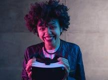 拿着VR设备的微笑的妇女 免版税库存照片