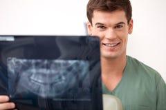 拿着X-射线的愉快的微笑的人牙医 图库摄影