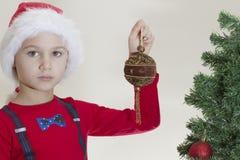 拿着xmas玩具的圣诞老人盖帽的不快乐的疲乏的男孩在圣诞树附近 免版税库存照片