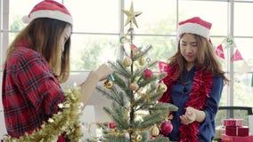 拿着xmas装饰品为的愉快的亚裔妇女在她的办公室装饰圣诞树 股票录像