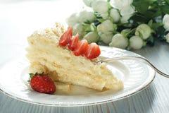 拿破仑蛋糕片断在板材的装饰了用一个红色成熟草莓,在它旁边的花束 图库摄影