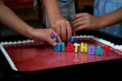 拿走由饥饿的孩子的五颜六色的生日蜡烛 免版税库存图片