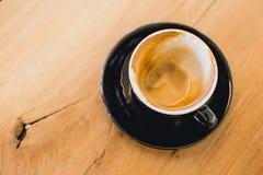 拿铁咖啡完成的饮料在黑杯子的在木头 免版税库存照片