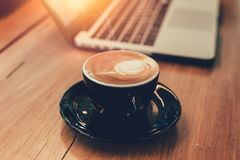 拿铁咖啡,当与便携式计算机一起使用时 免版税库存图片