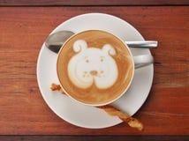 拿铁在木书桌上的咖啡艺术 免版税库存图片