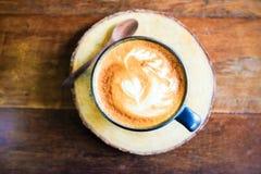 拿铁在木桌上的咖啡杯 免版税库存照片