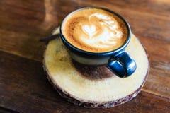 拿铁在木桌上的咖啡杯 库存照片