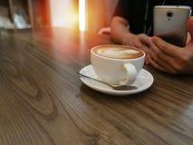 拿铁在木桌背景和人usi的艺术咖啡 免版税库存图片