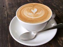 拿铁或热奶咖啡在木书桌上 免版税图库摄影