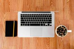 拿铁膝上型计算机和笔记薄与铅笔木表面上 免版税库存照片