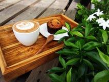拿铁艺术咖啡,木匙子和香蕉巧克力杯子结块 免版税库存照片